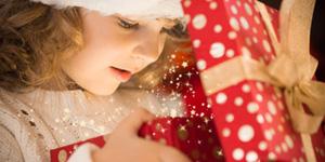 Kleines Mädchen öffnet Geschenk