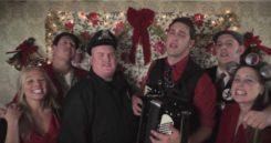 Gut gelaunte Menschen singen und spielen vor geschmückter Kulisse Weihnachtslieder